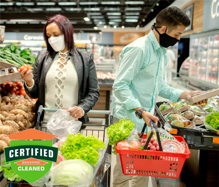 Two adults shopping the produce section of a grocery store with masks on. Green Certified: SERVPRO Cleaned logo in bottom