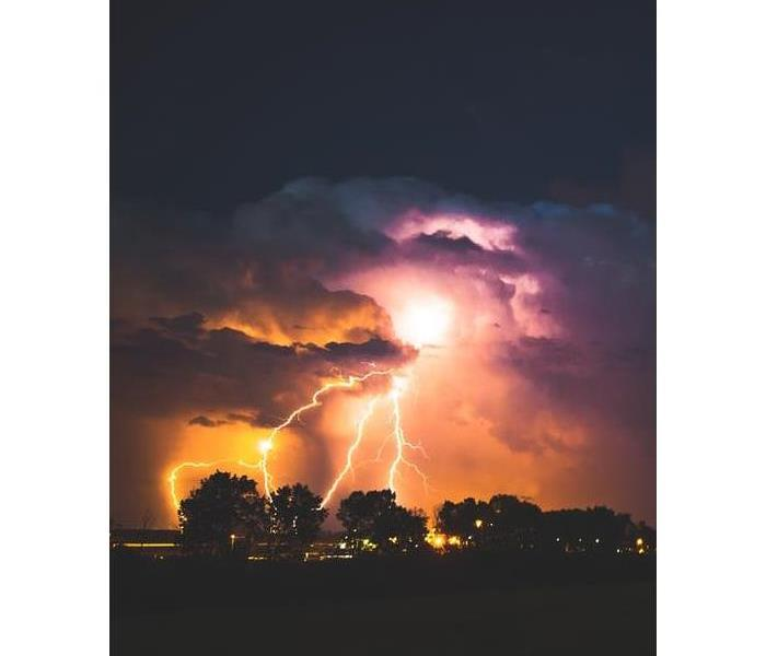 Nighttime storm with a lightening strike over several houses