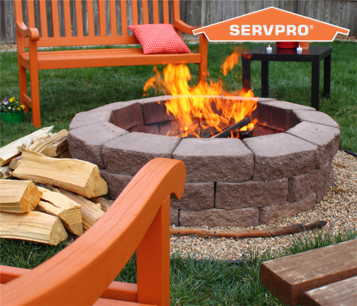 A lit firepit in the middle of a circle of orange outdoor furntiture. Orange SERVPRO logo in top right corner