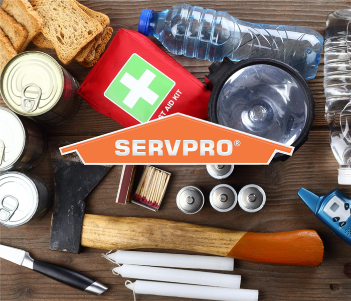 Photo taken from above looking down on emergency supplies on a table. Orange SERVPRO Logo in center of photo