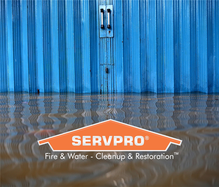 Flood water in front of a blue, metal sided building. Orange SERVPRO logo at the center bottom of photo