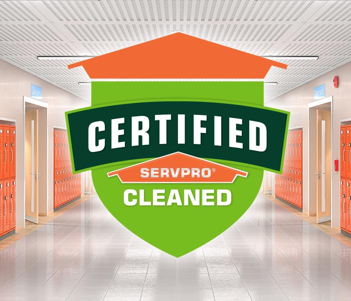 "Graphic of a SERVPRO shield that says ""Certified SERVPRO Cleaned"" with a school hallway in the background with orange lockers"